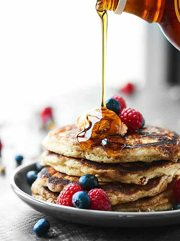 maple syrup being drizzled on stack of pancakes on plate