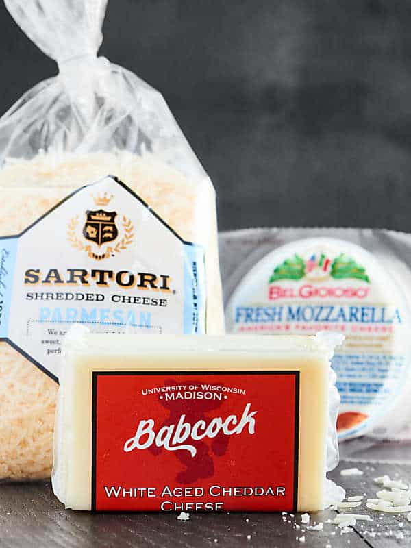 3 packages of cheese: parmesan, white cheddar, mozzarella