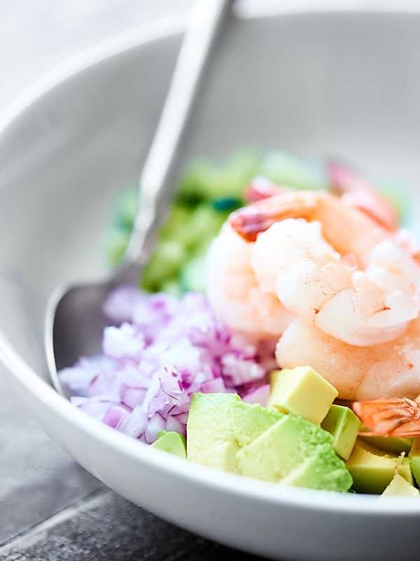 shrimp avocado salad ingredients in bowl closeup