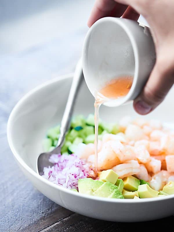 This Shrimp Avocado Salad Recipe is perfect for hot summer days! It's an EASY, cold, no-cook, healthy, refreshing salad full of shrimp, avocado, cucumbers, sun dried tomatoes, lemon juice, spices, and more! showmetheyummy.com #shrimp #avocado