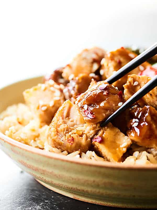Piece of turkey being taken out of teriyaki turkey tenderloin dish with chopsticks