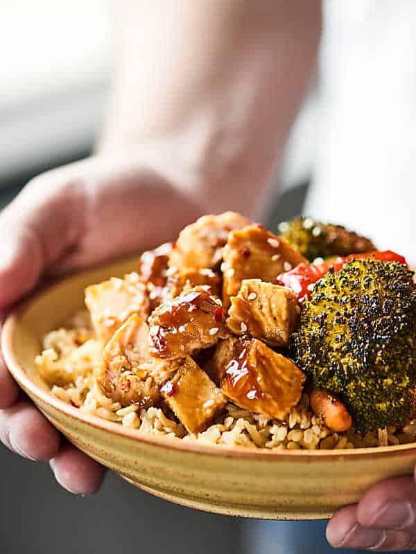 Plate of teriyaki turkey tenderloin with veggies and brown rice being held