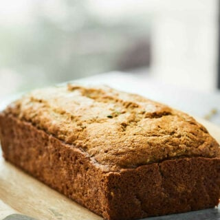 Tons of zucchini on your hands? Vegan Zucchini Bread tooooo the rescue! It's tender, it's moist, and it's loaded with cozy cinnamon, sweet brown sugar, coconut oil, and of course, plenty of zucchini! showmetheyummy.com #zucchinibread #vegan