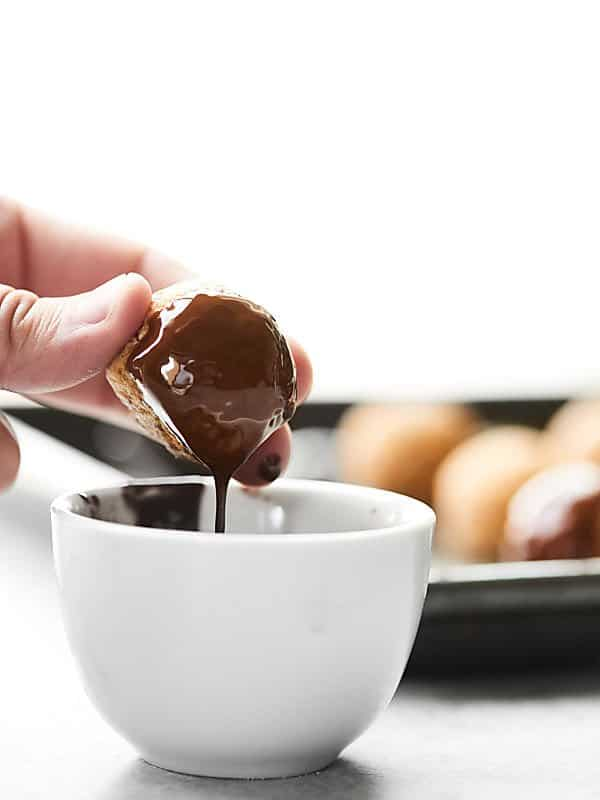lara bar bite being dipped in bowl of melted chocolate