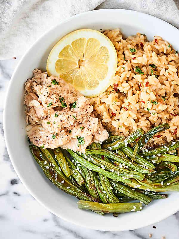 lemon pepper salmon, coconut brown rice, roasted green beans, and lemon slice in bowl above