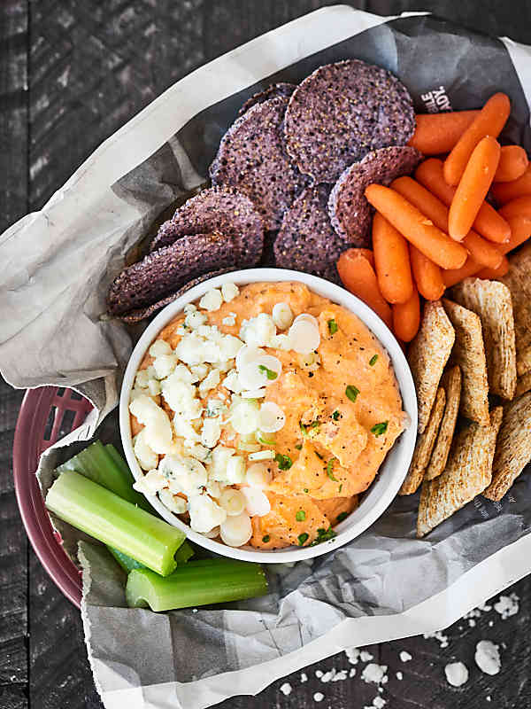 slow cooker cheesy buffalo chicken dip in bowl with basket of veggies, crackers, and chips above