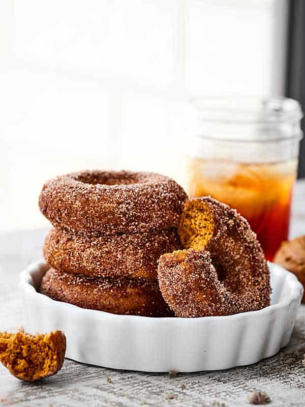 This Easy Baked Pumpkin Donuts Recipe is the perfect way to celebrate the start of fall. Tender, perfectly spiced donuts smothered in either a maple glaze or cinnamon sugar! showmetheyummy.com #bakeddonuts #pumpkindonuts