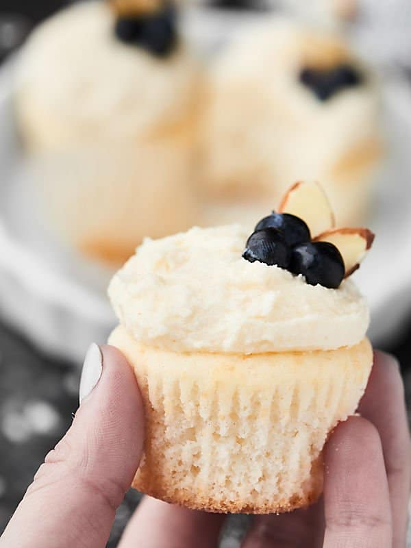 cupcake with vanilla frosting, sliced almonds, and blueberries held