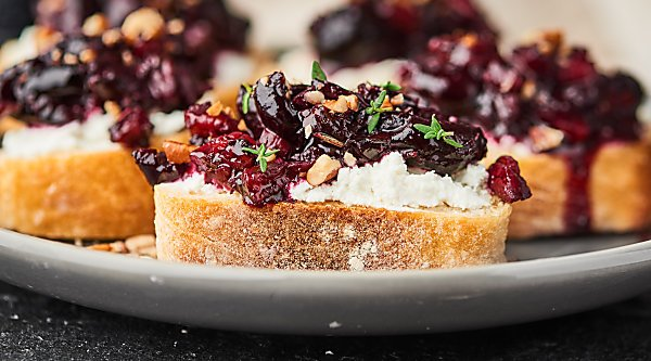 A twist on a classic, this Cherry Bruschetta is the perfect holiday appetizer. Full of sweet dark cherries, pecans, rosemary, thyme, and pinot noir, it comes together in minutes and is paired with a chewy baguette and tangy goat cheese! showmetheyummy.com Recipe made in partnership w/ @BarefootWine #bruschetta #holidayappetizers