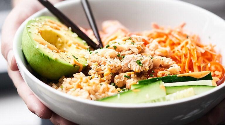 Spicy tuna roll bowl with chopsticks held