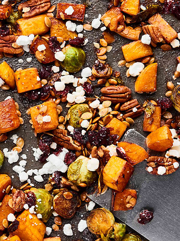roasted veggies, feta, pecans, and dried cranberries on baking sheet above
