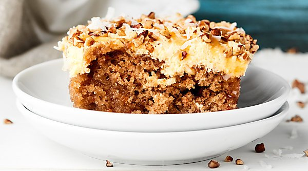 Cake mix kicked up a notch to make this Carrot Poke Cake Recipe! Carrot cake is drizzled with cream of coconut then smothered in a homemade caramel cheesecake cool whip frosting. showmetheyummy.com