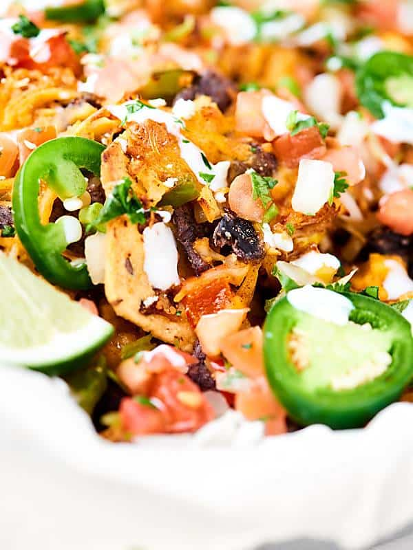 These Loaded Chicken Nachos have 12 layers! and are full of tender veggies, flavorful chicken, beans, corn, and TONS of cheese. Surprisingly quick, easy and delicious! showmetheyummy.com