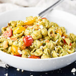 This simple Pesto Pasta Salad is loaded with pasta shells, fresh pesto, salty bacon, crumbly feta, juicy tomatoes, and crunchy cashews! showmetheyummy.com