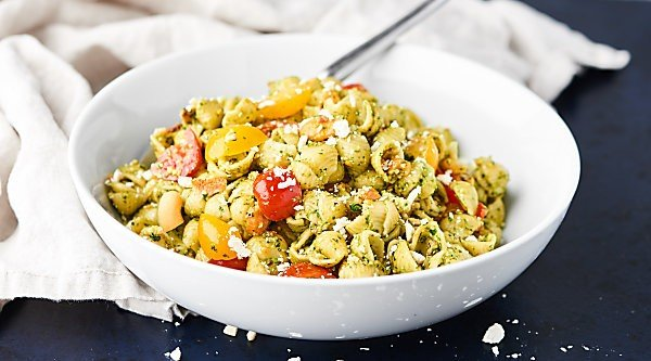 This simple Pesto Pasta Salad is loaded with pasta shells, fresh pesto, salty bacon, crumbly feta, juicy tomatoes, and crunchy cashews! showmetheyummy.com