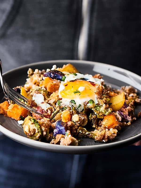 breakfast hash on plate held