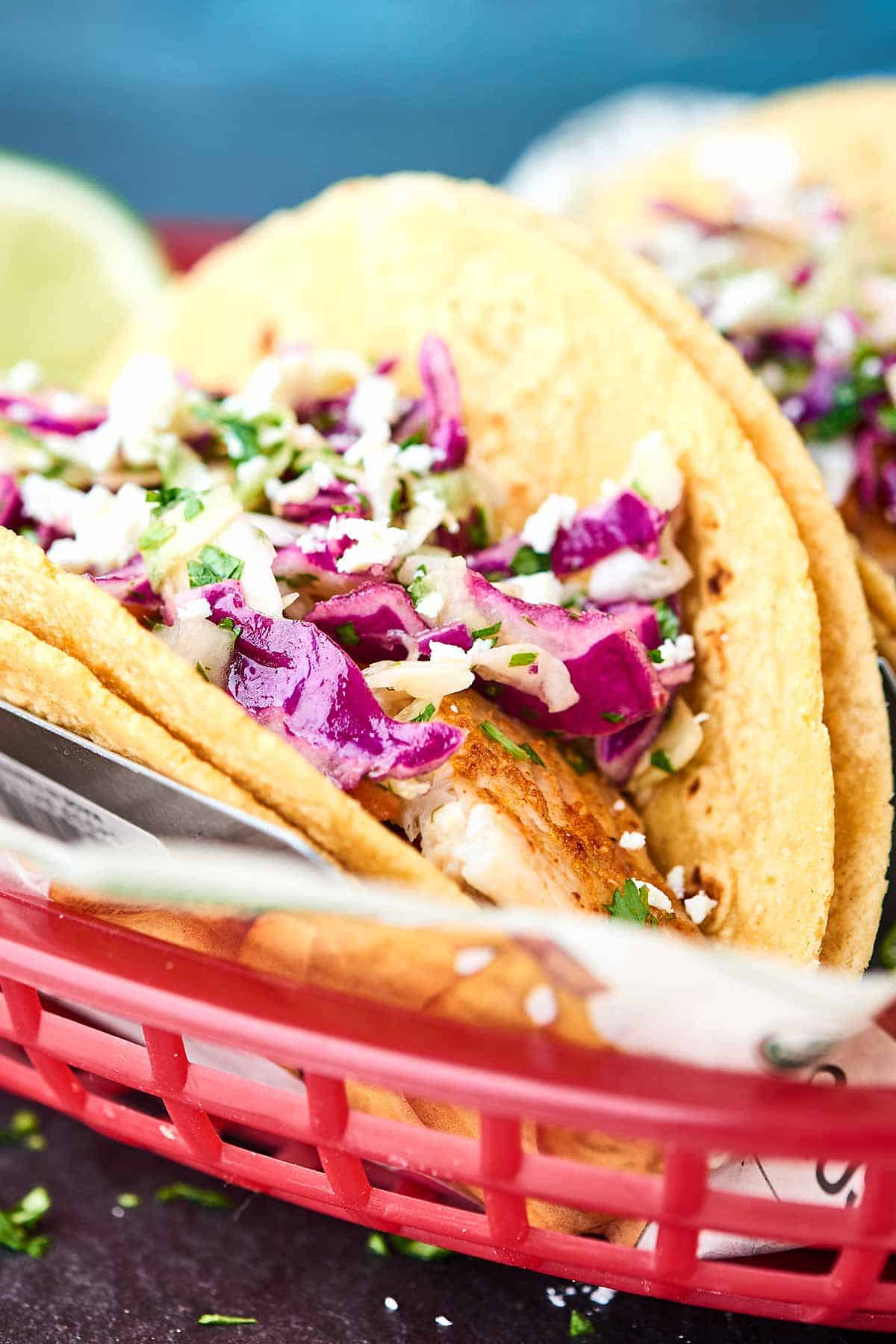 Healthy Baked Fish Tacos! Tilapia + spices + loads of lime all piled into a corn tortilla and topped with a fresh, crunchy slaw! Healthy easy deliciousness for the win! showmetheyummy.com #fishtacos #healthy #bakedfishtaco