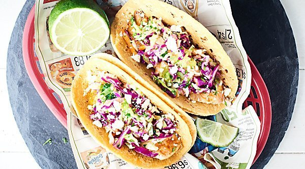Healthy Baked Fish Tacos! Tilapia + spices + loads of lime all piled into a corn tortilla and topped with a fresh, crunchy slaw! Healthy easy deliciousness for the win! showmetheyummy.com