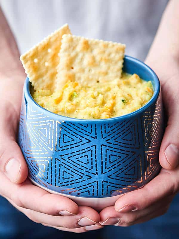 mug of skinny broccoli cheese soup with saltine crackers held two hands