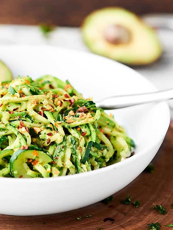 This Avocado Pesto Recipe is vegan, gluten free, oil free, and oh yeah, absolutely delicious! Packed with fresh herbs, garlic, pistachios, nutritional yeast, and more! showmetheyummy.com