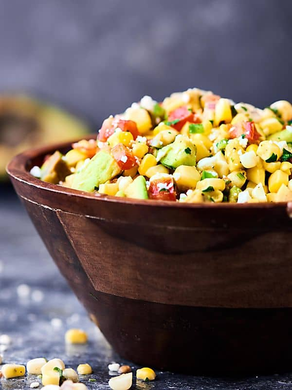 Bowl of grilled corn avocado salsa side view