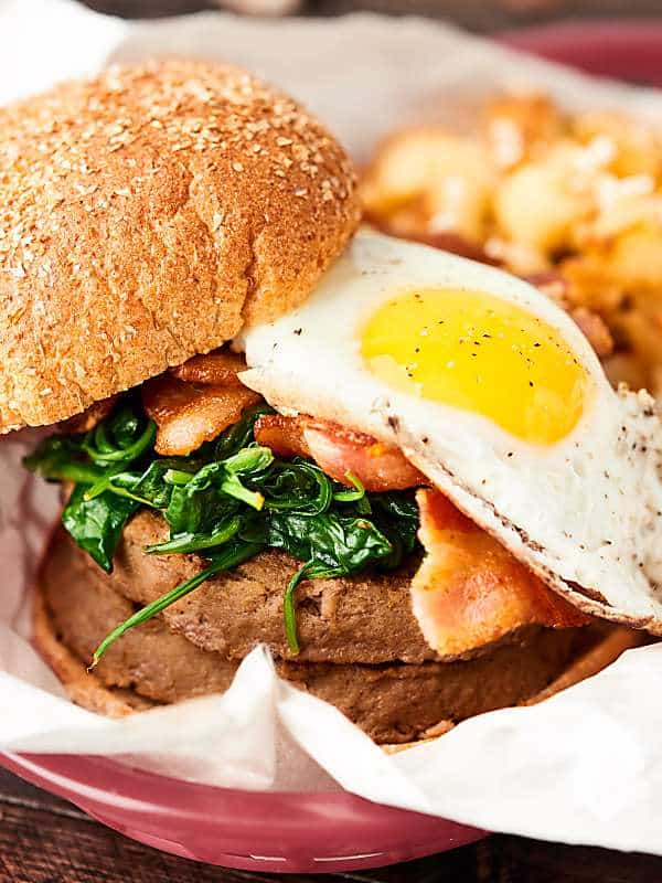 #ad Turkey Brunch Burger Recipe. Because why should grilling JUST be for dinner?! A grilled turkey burger topped with cheese, spinach, bacon, a gooey egg, and a drizzle of maple syrup! showmetheyummy.com #SwitchCircle #JennieO