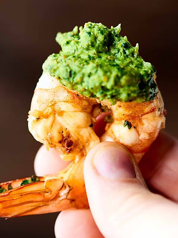 piece of grilled shrimp being held with avocado pesto sauce on it