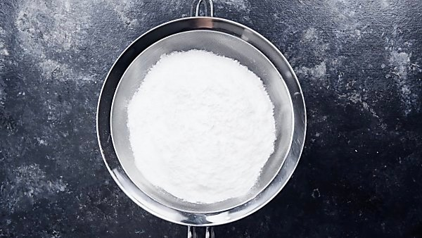Powdered sugar being sifted through sieve