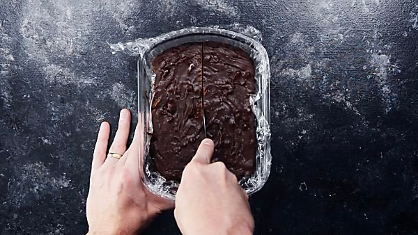Chocolate fudge being cut with butter knife