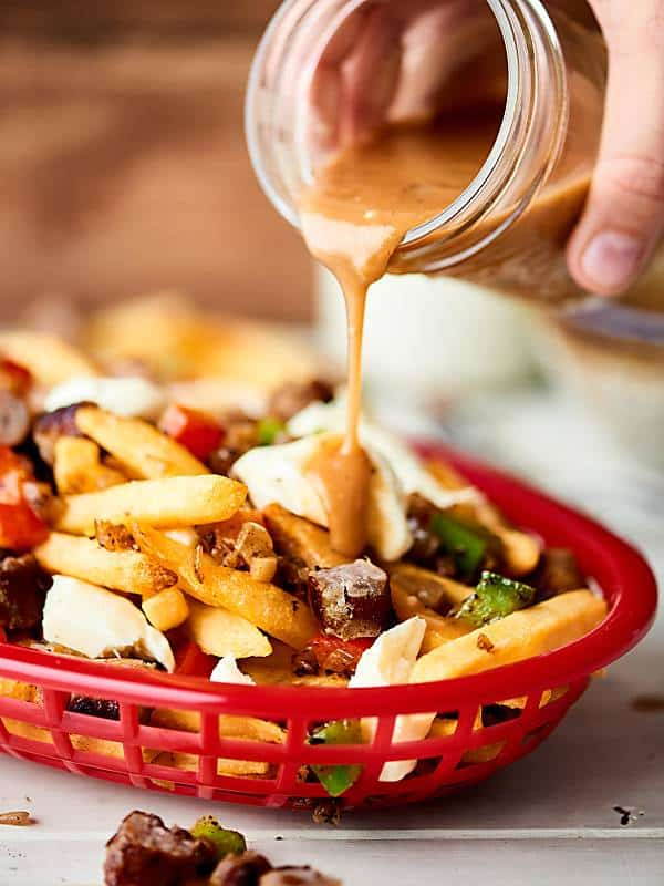 poutine gravy being drizzled over basket of poutine