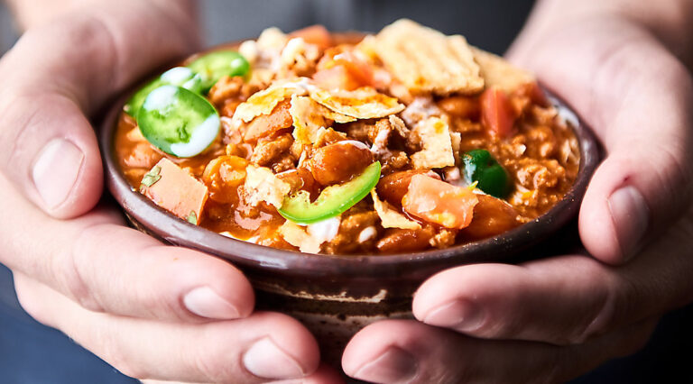 Bowl of chili held in two hands