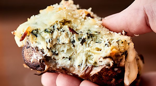 #ad Healthier Spinach Artichoke Stuffed Mushrooms, the perfect appetizer for easy entertaining! Mushroom caps stuffed with a greek yogurt spinach artichoke dip, topped with mozzarella, and baked to gooey perfection! showmetheyummy.com Made in partnership w/ @laterrafina