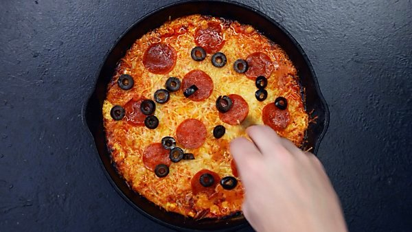 Black olives being layered on baked, loaded pizza dip