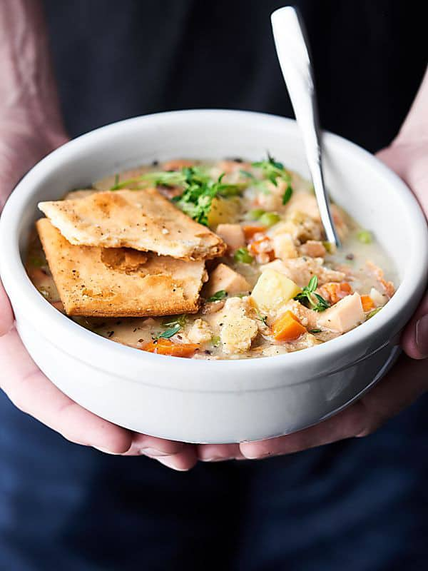 bowl of healthy turkey pot pie soup held two hands