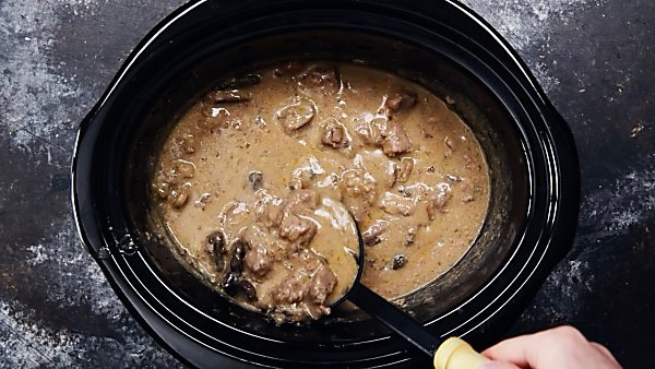 Finished beef stroganoff ladle being taken out of crockpot