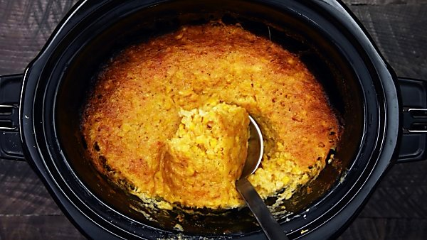 finished slow cooker corn pudding being scooped with ladle