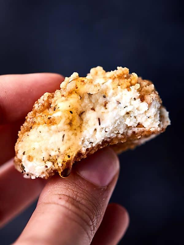 warm walnut goat cheese bite held