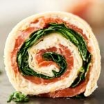 #ad These Smoked Salmon Pinwheels are perfect for easy and elegant holiday entertaining. Quick and easy to make with only four ingredients: tortillas, a lemon pepper and asiago spread, smoked salmon, and spinach! showmetheyummy.com Made in partnership w/ @laterrafina