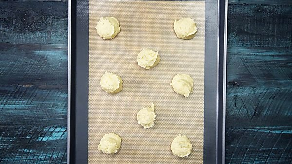 sugar cookie dough scooped on baking sheet