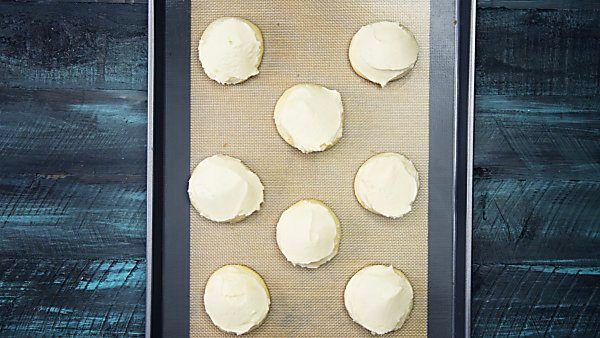 grandma's best sugar cookies frosted on baking sheet