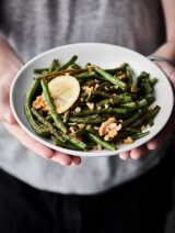 These Roasted Green Beans are easy, healthy, vegan, gluten free, and SO tasty! Green beans are tossed with coconut oil, garlic powder, onion powder, salt, pepper, lemon juice, and walnuts and roasted to perfection!showmetheyummy.com #greenbeans #vegan