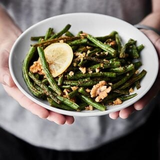 These Roasted Green Beans are easy, healthy, vegan, gluten free, and SO tasty! Green beans are tossed with coconut oil, garlic powder, onion powder, salt, pepper, lemon juice, and walnuts and roasted to perfection! showmetheyummy.com #greenbeans #vegan