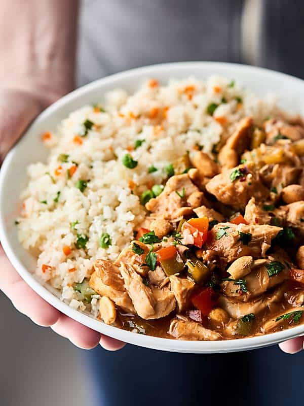 Plate of slow cooker kung pao chicken with rice held