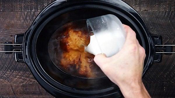 cornstarch slurry being whisked into sauce