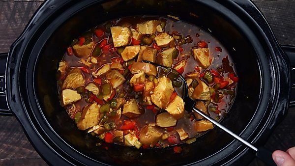 finished slow cooker kung pao chicken being served with spoon