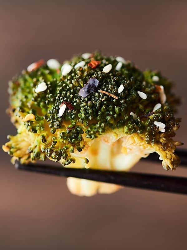 Piece of broccoli held with chopsticks