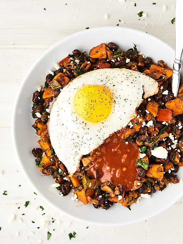 This Breakfast Burrito Bowl Recipe is full of sweet potatoes, peppers, onion, spinach, mushrooms, garlic, black beans, and spices. Topped with a fried egg, salsa, and greek yogurt! Healthy. Meatless. Gluten Free. Perfect for meal prep! Can be vegan! showmetheyummy.com #breakfast #healthy #burrito