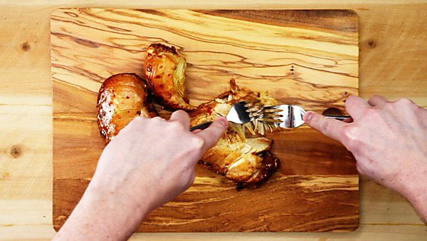 Chicken being shredded on cutting board