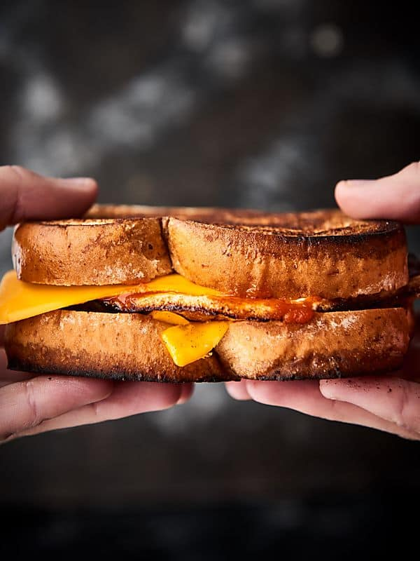 breakfast grilled cheese sandwich held two hands