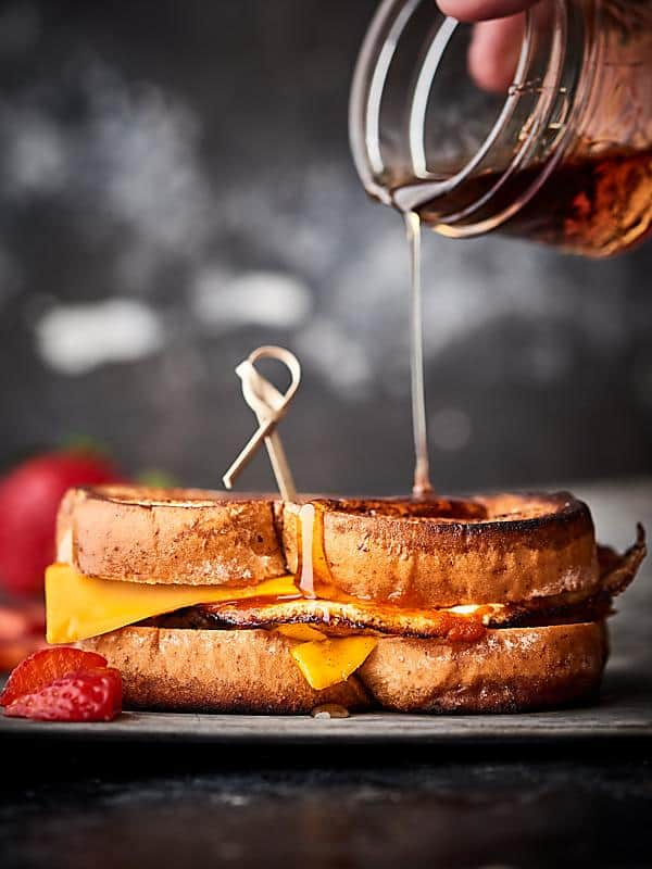 maple syrup being drizzled over breakfast grilled cheese sandwich on plate
